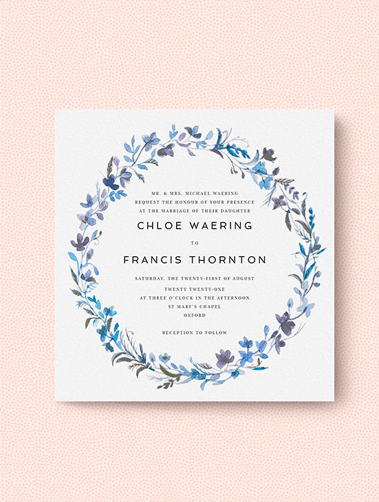 A classic wedding invitation design personalised with a blue floral wreath