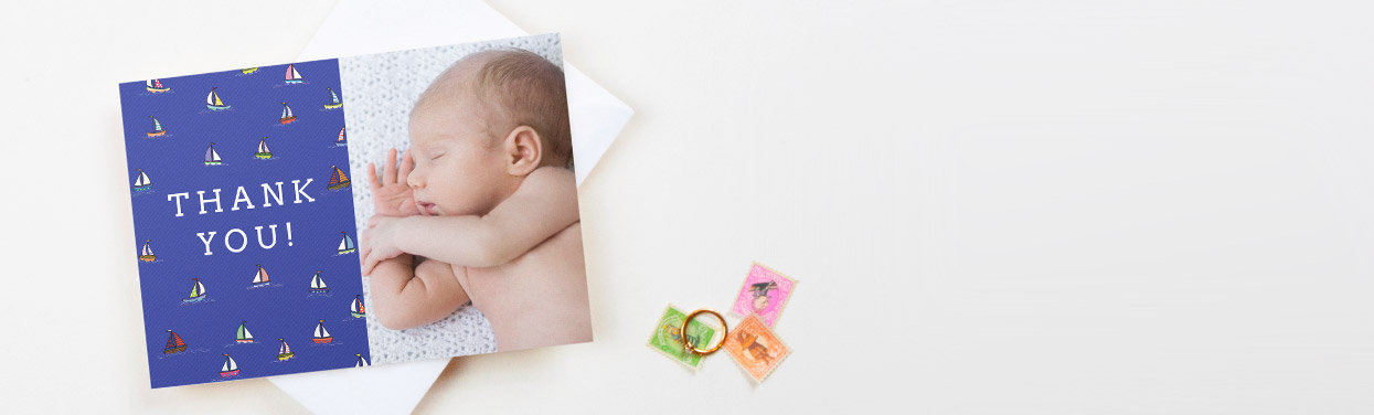 A baby thank you card design. The thank you card is printed with a photo of a baby boy. It has a blue nautical design next to the photo.
