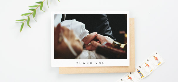 "A simple christening thank you cards with a large baptism photo. ""Thank you"" is written in capitals at the bottom of the card."