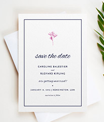 A classic wedding save the date design. The save the date card has a traditional blue border, surrounding a simple flower motif and elegant text.