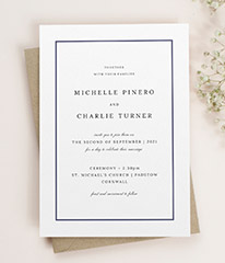 A classic wedding invitation design. The wedding invitation has a traditional navy-blue border and elegant type face.