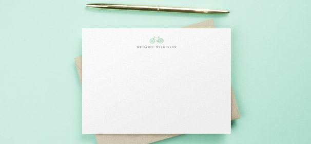 A personalised correspondence card for a man. It is a white note card with a blue bike design above and man's printed name.
