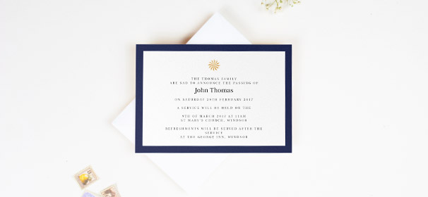 A funeral invitation card printed on a white card with a navy-blue border. There is a golden sundial in the middle. The invite is sat on an envelope.