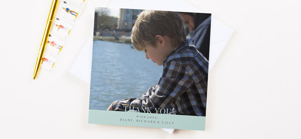 A square first holy communion thank you card design. It has a photo of a young boy, with a light blue banner at the bottom of the thank you card.