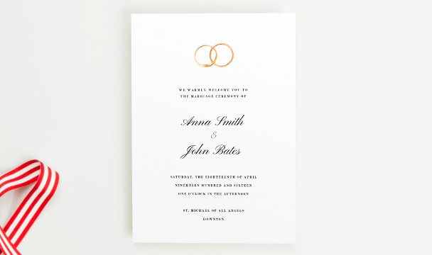 A beautiful wedding order of service booklet printed with two golden wedding rings at the top of the front cover.