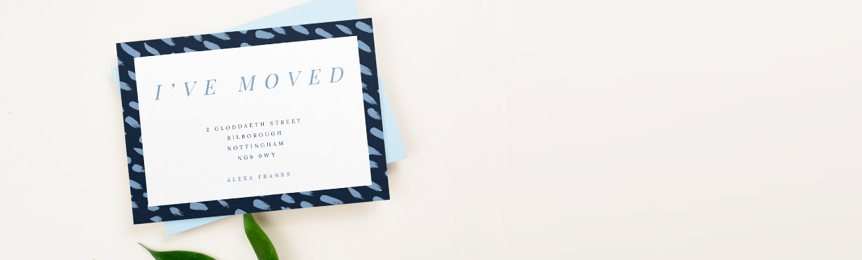 Printed change of address card with a blue envelope underneath. The moving home card is printed with a navy border and light blue paint strokes.