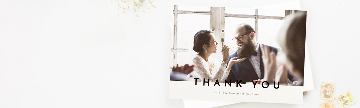 "A printed wedding thank you card showing a married couple eating their wedding cake. The card reads ""Thank You"""