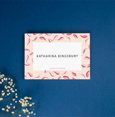 A table place card for weddings, personalised with a wedding guest's name. It is a floral place card design, sat on a navy-blue background