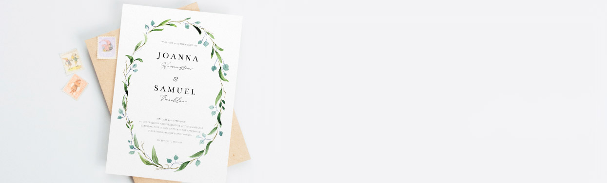 A personalised wedding invite design. It is a watercolour floral design in green and blue with cute printed fonts. It sits on a brown envelope.
