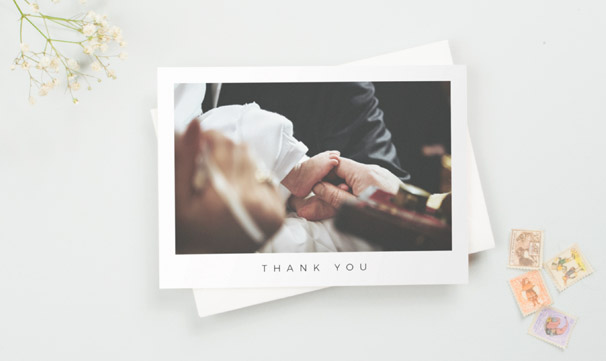 "A christening thank you card with a photo from the baptism ceremony. The thank you card has ""Thank you"" printed underneath the photo."