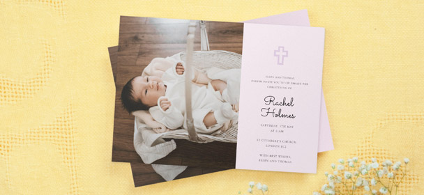 A religious christening invitation card with a photo of a baby girl. The invite is printed with a purple crucifix.