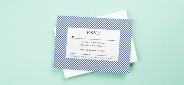 A wedding RSVP card sat on a little envelope. The response card is printed with a modern, blue and white border.