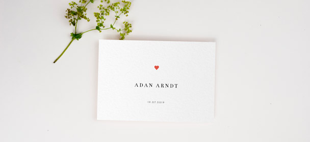 A wedding table place setting card design. The printed tent card is personalised with a wedding guests name. It has a simple heart design.