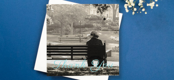 "A funeral thank you card design with a blue, cursive ""Thank you"" written over a full-page photo."