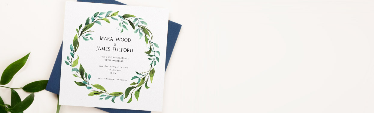 A customised wedding invitation design. This wedding invitation is printed with a green watercolour wreath design. The card sits on a blue envelope.