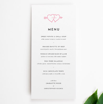 A simple wedding menu design. It is a tall and thin wedding menu card with two pink hearts at the top. It lists the wedding meal courses.