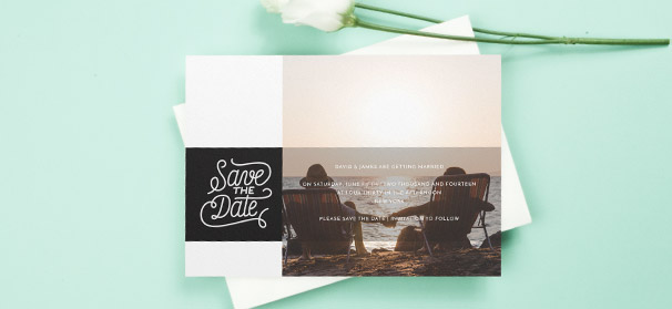 "A wedding save the date design, printed with a photo of the engaged couple. ""Save the Date"" is stylistically written in white on a black background."