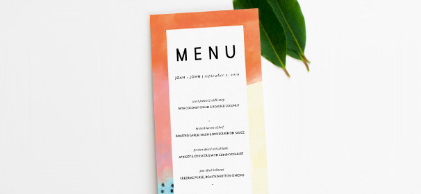A printed modern wedding menu design. The menu has an abstract orange and yellow border, with the wedding menu text written in black.