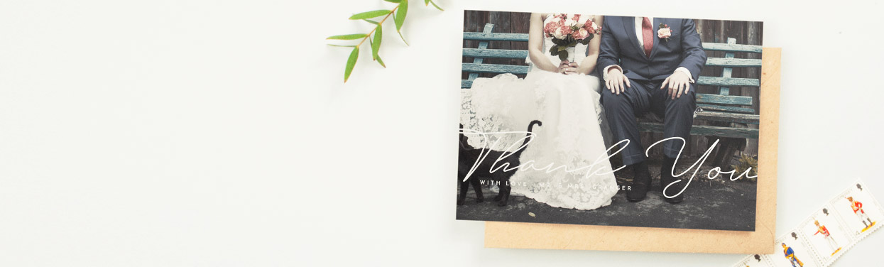 A simple wedding thank you card design with a full-page photo of the bride and groom. 'Thank you' has been printed in white over the couple's photo.