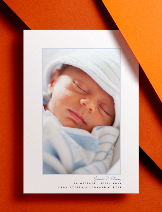 A baby birth announcement card with printed toy animals sat on a brown envelope. The card shows a photo  and birth details of a new-born baby girl.