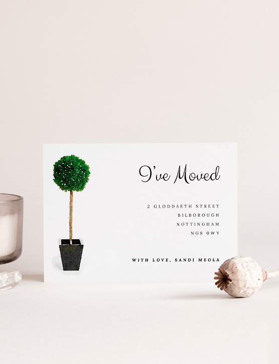 Printed change of address card with a blue envelope underneath. The moving home card is printed with a navy border and light blue paint strokes