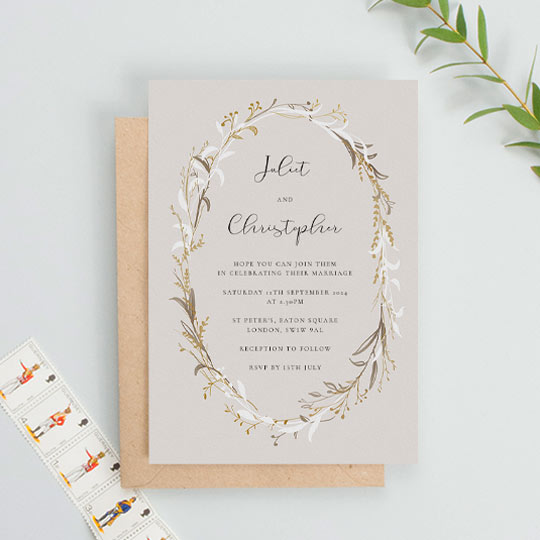 A rustic floral wedding invitation made of an unusual gold, white and brown wildflower wreath. This is a portrait wedding invitation with an earthy background and modern text.