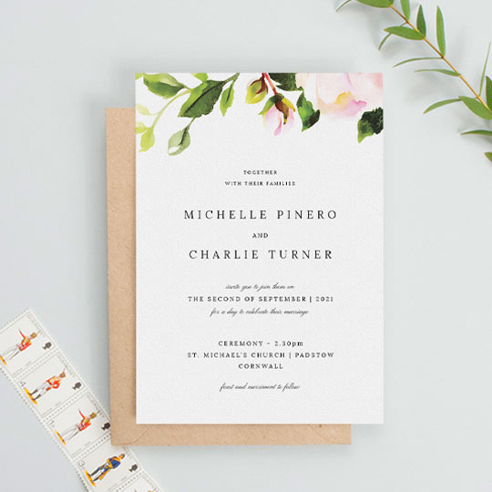 A classic floral wedding invitation which is predominantly white, apart from a painted rode and leaf element at the top of the card. The rest of the card is printed with a black, classic font arrangement.