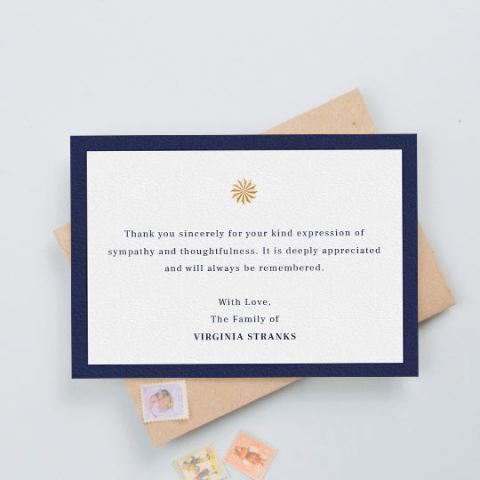 A funeral thank you card with a thick, navy blue border and an orange/gold sundial icon in the middle. The card has a personalised message of thanks in the middle