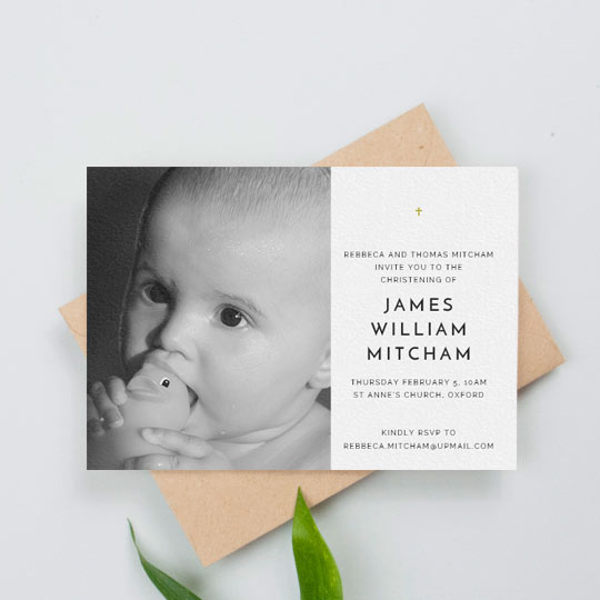 A simple christening invitation with a baby photo on the right-hand side. There is a black and white photo on the left of the christening invitation. The right-hand side has a small, gold crucifix.