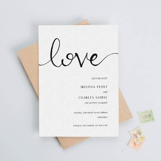 "A classic, simple wedding save the date card. It is a black and white save the date card with the word ""love"" handwritten at the top. The wedding information is printed on the bottom written of the save the date."