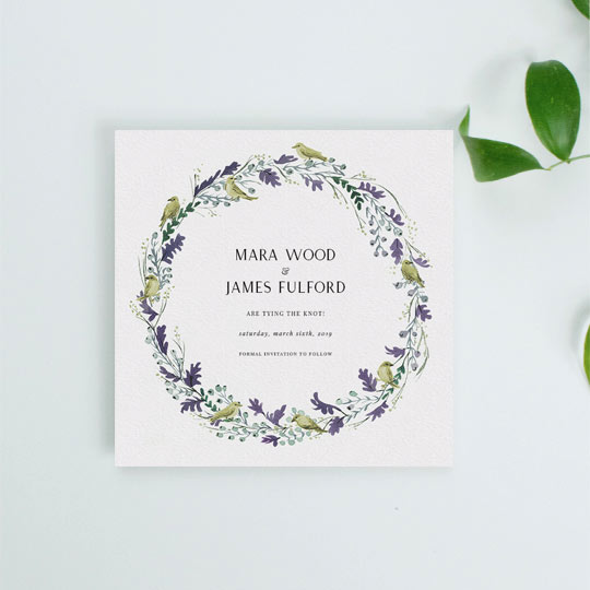 A classic wedding save the date card with a purple and gold floral wreath. The wreath has wild birds and oak leaves painted in it. The names of an engaged couple, and the wedding details are printed at the bottom.