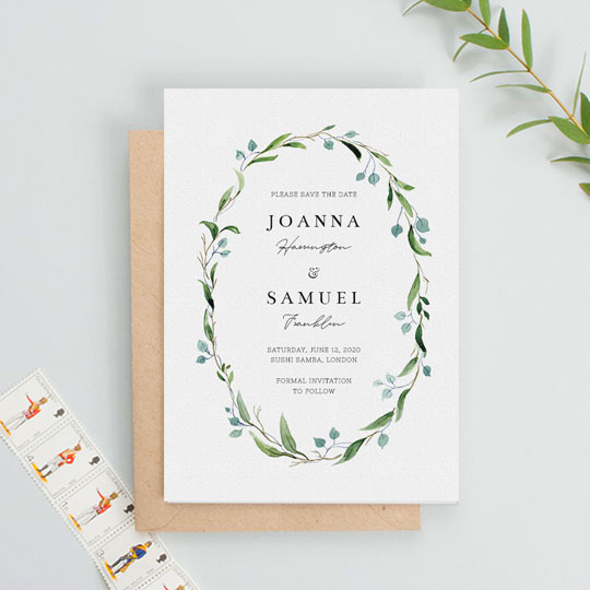 A floral, classic wedding save the date card. It is a white card with a green and blue watercolour floral wreath. In the middle of the floral wreath, the save the date has the details of a wedding printed.