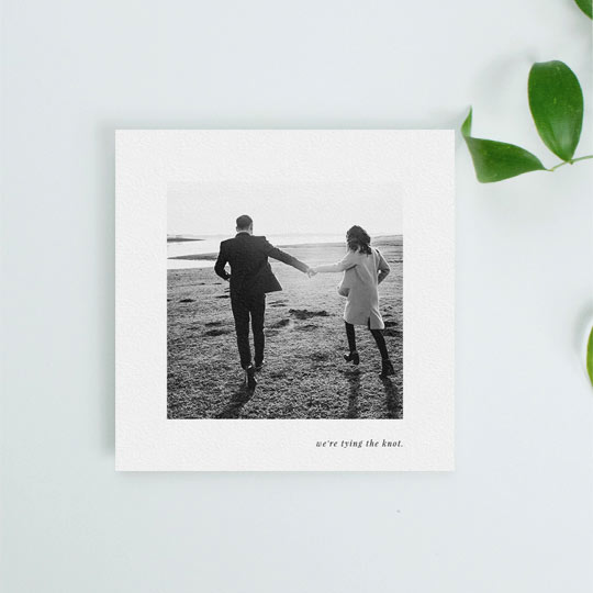 "A simple and classic wedding save the date card with photos. It has a medium sized photo in black and white in the centre of the card. Underneath the save the date photo, the words ""we're tying the know"" are printed in black."