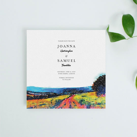 A country, rustic wedding save the date card. It is predominantly white with a watercolour-painted countryside vista at the bottom. The details of an upcoming wedding are printed at the top in a black font.