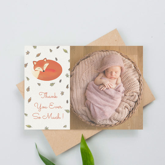 "A landscape baby thank you card with a sleep fox surrounded by autumn leaves. It reads ""Thank you ever so much"". There is a picture of a baby girl to the right-hand side."
