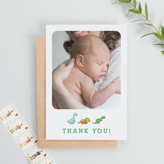 A portrait baby thank you card with dinosaurs underneath a baby photo. The photo on the thank you card takes up most of the design.