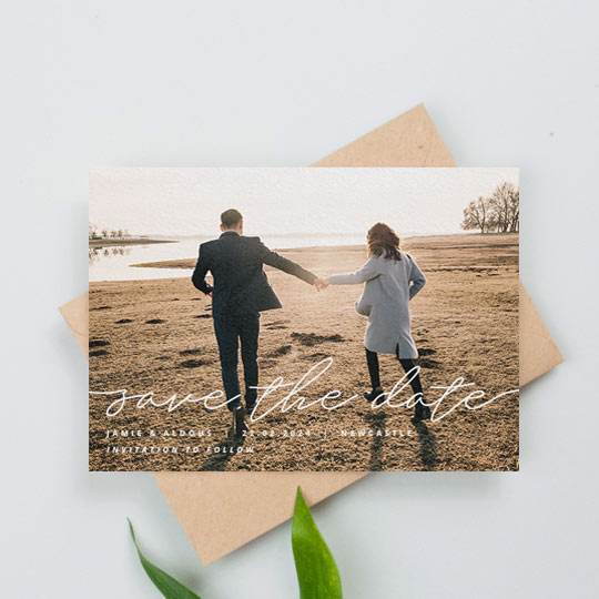 "A landscape, modern wedding save the date card with photo. The save the date card has full-page photo with a handwritten ""save the date"" written across the bottom. The engaged couple's names and the details of the wedding are printed below."