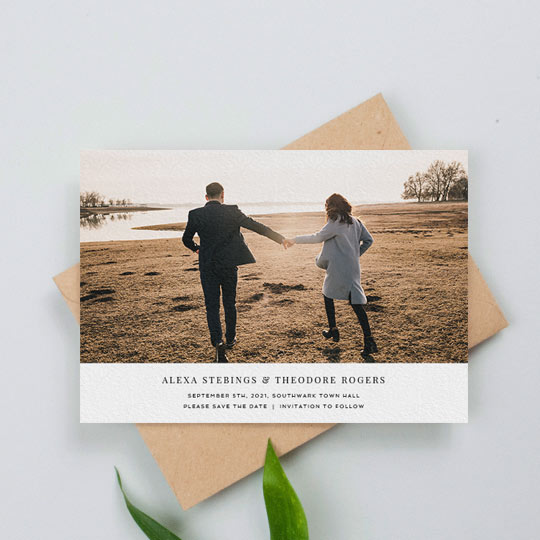 And really elegant wedding save the date photo card. The card has a large, colour photo of engaged couple. Underneath the photo, the save the date has details about an upcoming wedding.