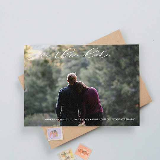 "An elegant wedding save the date card with a full page photos and a tasteful font written at the top. The font reads ""Save the Date""."