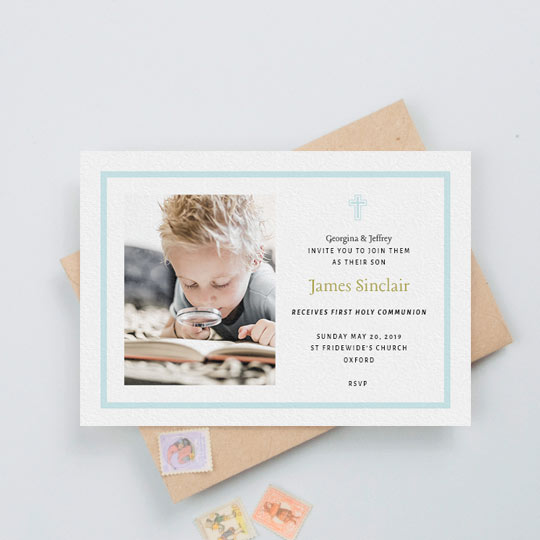 A first holy communion invitation for a young boy. It has a baby blue border and blue crucifix. The card has a photo of a boy on the left. His name is written in a gold font