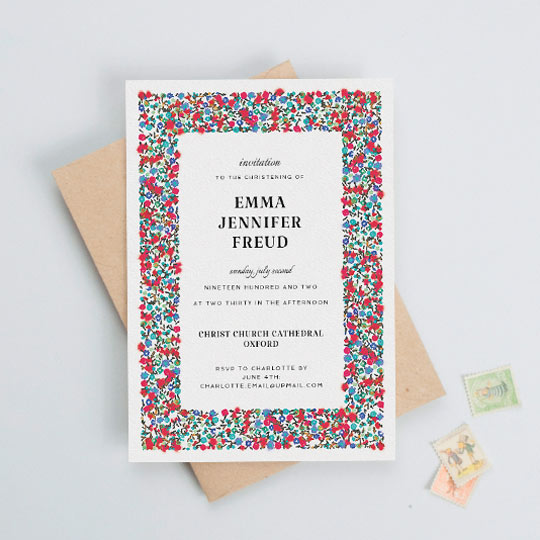 A white christening invitation card with a colourful red and blue floral border. There is black text in the middle with details of a baby girl and her christening.