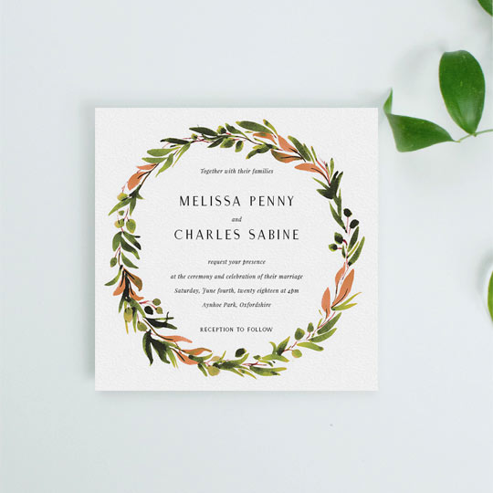 A square wedding invitation with a classic floral wreath. The invitation's wreath is painted with shades of greens and oranges. The font is classic and simple.