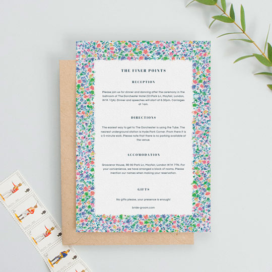 A floral wedding insert sheet containing information on an upcoming wedding. The information font is blue and classic.