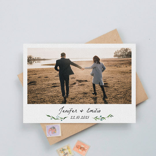 A simple, floral wedding save the date card with photos. It has small blue and green floral details either side of the printed date of a wedding. Above the date is the name of an engaged couple. At the top of the wedding save the date card is a photo of the engaged couple.