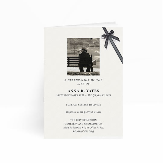 An elegant, multi-paged order of service booklet for a funeral. The program is predominantly white, with a painted, black ribbon running across the top-right hand corner. There is a black and white photo on the front cover.