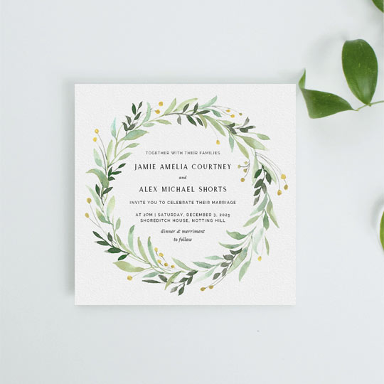 A spring floral wedding invitation. This wedding invitation design had light green and mint leaves with small yellow flower buds. It has black wedding invitation text in the middle of the floral wreath.
