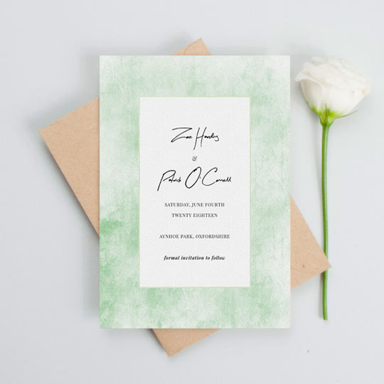 A rustic wedding save the date card with a worn green background. The centre of the save the date is white with black text detailing the particulars of an upcoming wedding.