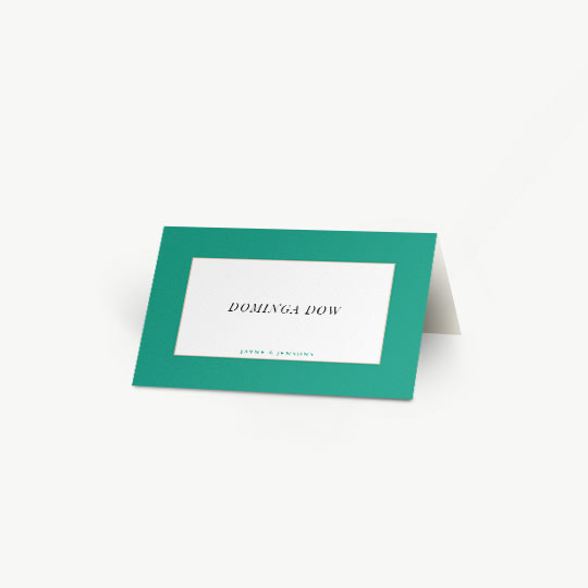A bold, green place card personalised with the name of a wedding guest. The name of the bride and groom is printed at the bottom in blue. The folded place card sits on a white table.
