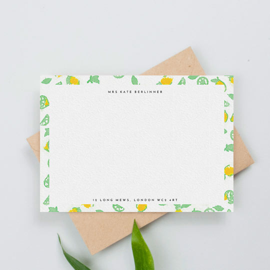 A personalised desk stationery note card with a lady's name printed at the top, and her address at the bottom. The card is surrounded by green and yellow lemons in a modern pattern.