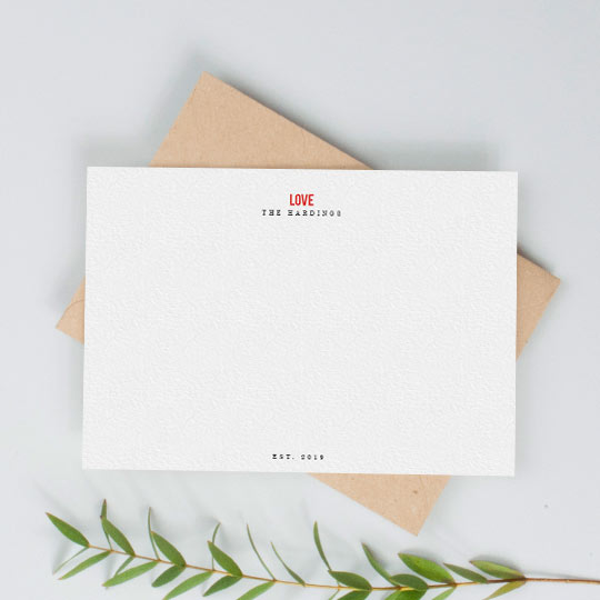 "A white, personalised desk note card. It is personalised with the names of a couple and has the word ""LOVE"" printed in red at the top of the note card."